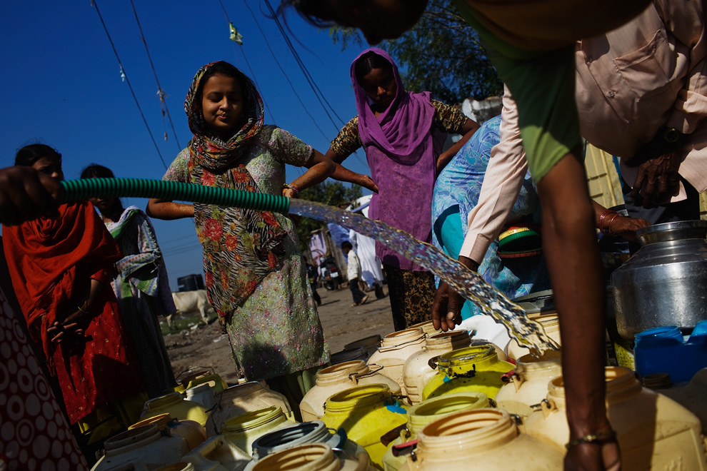 10. Женщины наполняют контейнеры чистой водой в Бхопале, которую сюда привозят, так как местная вода была загрязнена во время утечки газа на заводе «Union Carbide» 28 ноября 2009 года. (Daniel Berehulak/Getty Images)