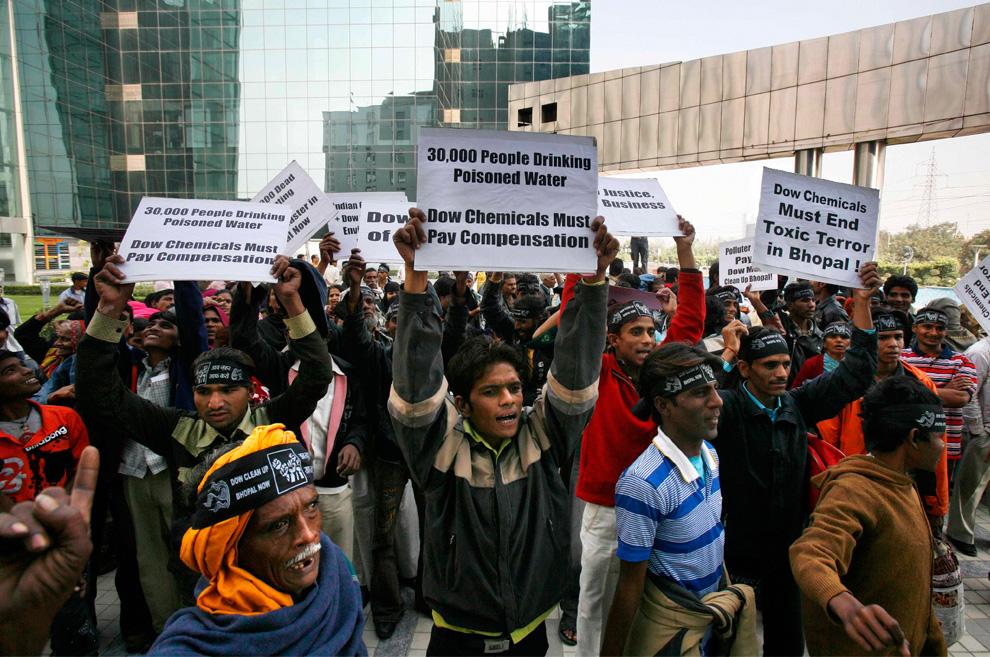 11. Активисты и выжившие в Бхопальской катастрофе 1984 года держат плакаты у офиса компании «Dow Chemical» в Нойде на окраине Нью-Дели в четверг 19 ноября 2009 года. Дочернее предприятие американской химической компании «Union Carbide» управляло заводом во время происшествия. Десятилетиями выжившие борются за снос завода, но их попытки натолкнулись на трудности, когда завод «Union Carbide» приобрела компания «Dow Chemical Co.» в 2001 году. Компания утверждает, что не несет ответственности за снос завода и ликвидацию последствий катастрофы. (Staffing/Manish Swarup)