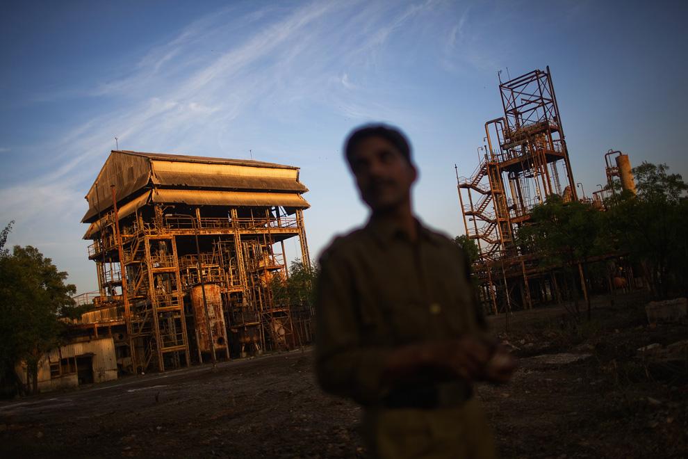14. Полицейский осматривает заброшенный завод «Union Carbide» 28 ноября 2009 года в Бхопале, Индия. (Daniel Berehulak/Getty Images)