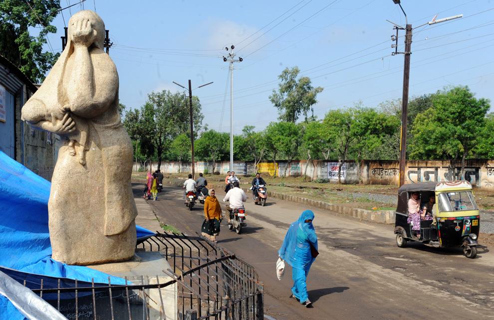 15.  Orang-orang berjalan melewati patung seorang ibu dengan anak yang sudah mati dalam pelukannya di Bhopal, 18 November 2009.  Warga kota dengan tampilan pahit dalam arah pabrik tua «Union Carbide», dimana pagi hari tanggal 3 Desember 1984 kebocoran gas dalam sekejap menewaskan ribuan orang.  Warga mengatakan bahwa setiap ulang tahun - ini adalah satu tahun trauma fisik dan psikologis, rumit kelalaian pemerintah dan perusahaan.  (RAVEENDRAN / AFP / Getty Images)