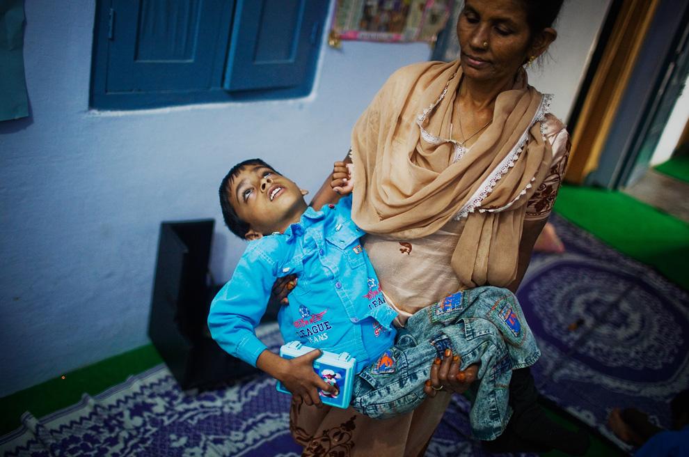 16. Нафиза Би – координатор клиники «Chingari Trust» - несет на руках 8-летнего Аннана 27 ноября 2009 года в Бхопале, Индия. Через 25 лет после утечки газа, ставшего причиной гибели тысяч невинных людей, последствия крупнейшей в мире техногенной катастрофы продолжают вредить жителям Бхопала. Аннан страдает церебральным параличом и лечится в клинике «Chingari Trust». (Daniel Berehulak/Getty Images)
