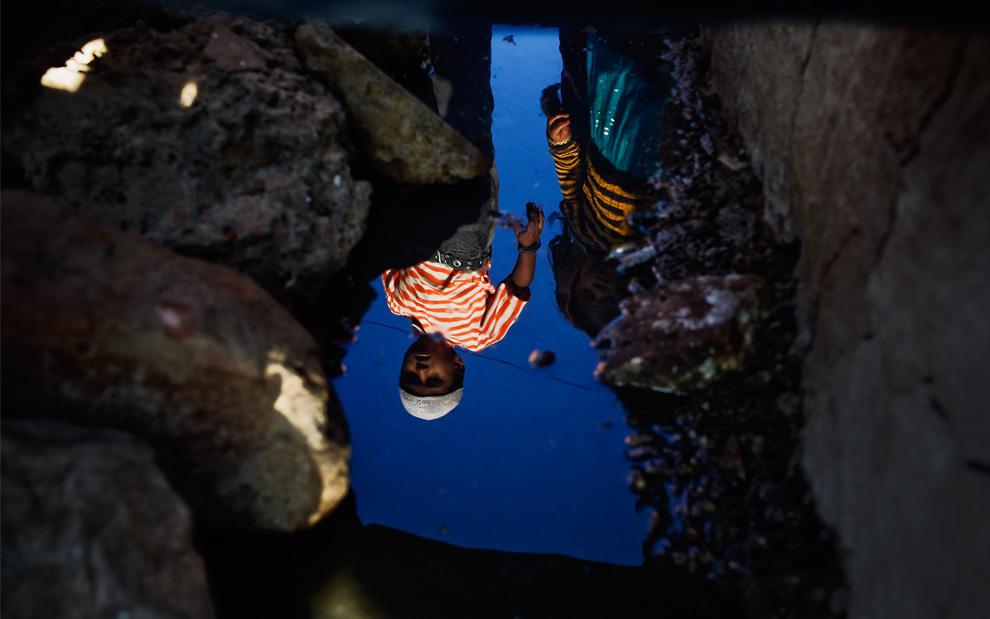 19. Дети отражаются в загрязненной грунтовой воде недалеко от заброшенного завода «Union Carbide» 28 ноября 2009 года в Бхопале, Индия. (Daniel Berehulak/Getty Images)
