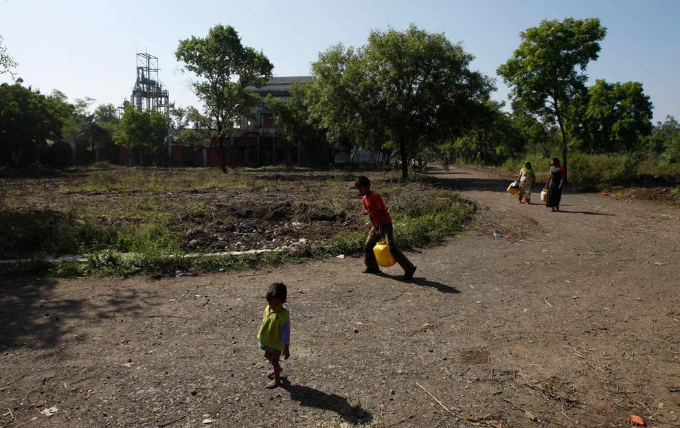 21.  Orang-orang wadah dengan air yang dikumpulkan dalam wilayah bekas pabrik «Union Carbide» di Bhopal, India, 21 November 2009.  (AP Photo / Saurabh Das)