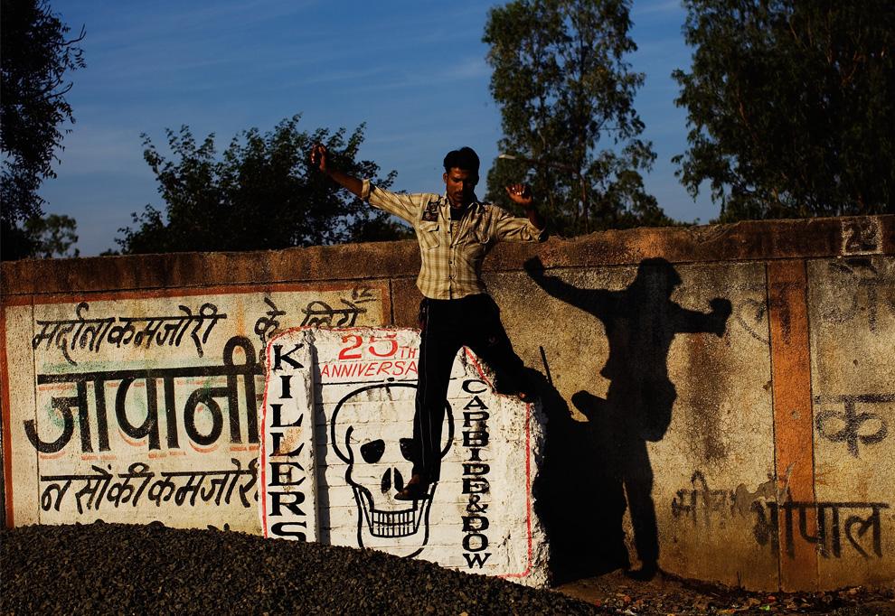 26. Мужчина спрыгивает с периметровой стены на территории завода «Union Carbide» 28 ноября 2009 года в Бхопале, Индия. (Daniel Berehulak/Getty Images)