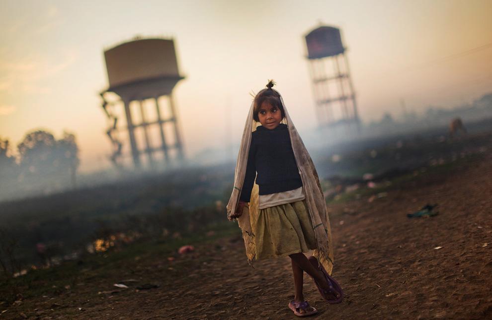 28.  Seorang gadis berdiri di samping menara air di dekat rumahnya di dekat pabrik «Union Carbide» November 27, 2009 di Bhopal, India.  (Daniel Berehulak / Getty Images)