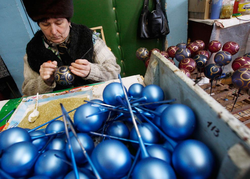 7. Женщина раскрашивает новогодние игрушки на заводе в поселке Клавдиео, Украина, 16 декабря 2009 года. (REUTERS/Gleb Garanich)