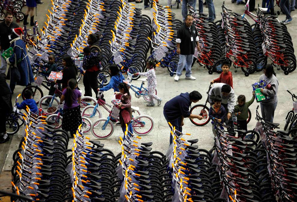 9. Доброволец центра « L.A. Dream Center» помогает мальчику выбрать новый велосипед в зале « L.A. Sports Arena» в Лос-Анджелесе 20 декабря 2009 года. Тысячи велосипедов и игрушек были розданы нуждающимся семьям во время благотворительной акции. (REUTERS/Danny Moloshok)