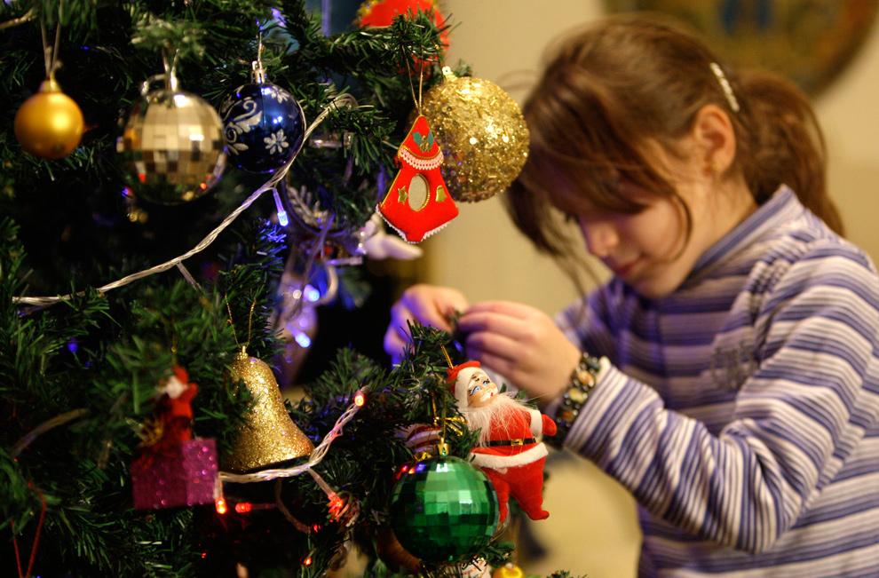11. Девочка украшает елку у себя дома в Багдаде 22 декабря 2009 года. (REUTERS/Saad Shalash)