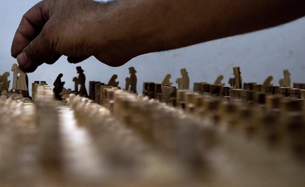 12. Палестинский рабочий ставит фигурки из оливкового дерева в сцену Рождества Христова на заводе в Вифлееме 21 декабря 2009 года. Искусство резьбы по оливковому дереву пришло в Вифлеем в 4-ом веке вместе со строительством Рождественского Собора, построенным рядом с гротом, где по легенде родился Иисус Христос. Монахи научили этому искусству местных жителей, и теперь многие жители Вифлеема или его окрестностей либо вырезают из оливкового дерева, либо продают его на материал. (AP Photo/ Tara Todras-Whitehill)