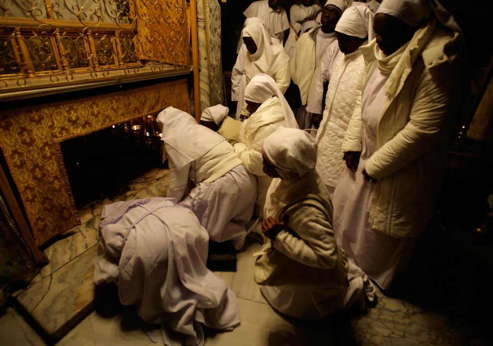 13. Нигерийские паломники молятся в гроте, где по легенде Дева Мария родила Иисуса в Рождественском соборе в Вифлееме 24 декабря 2009 года. (REUTERS/Ammar Awad)