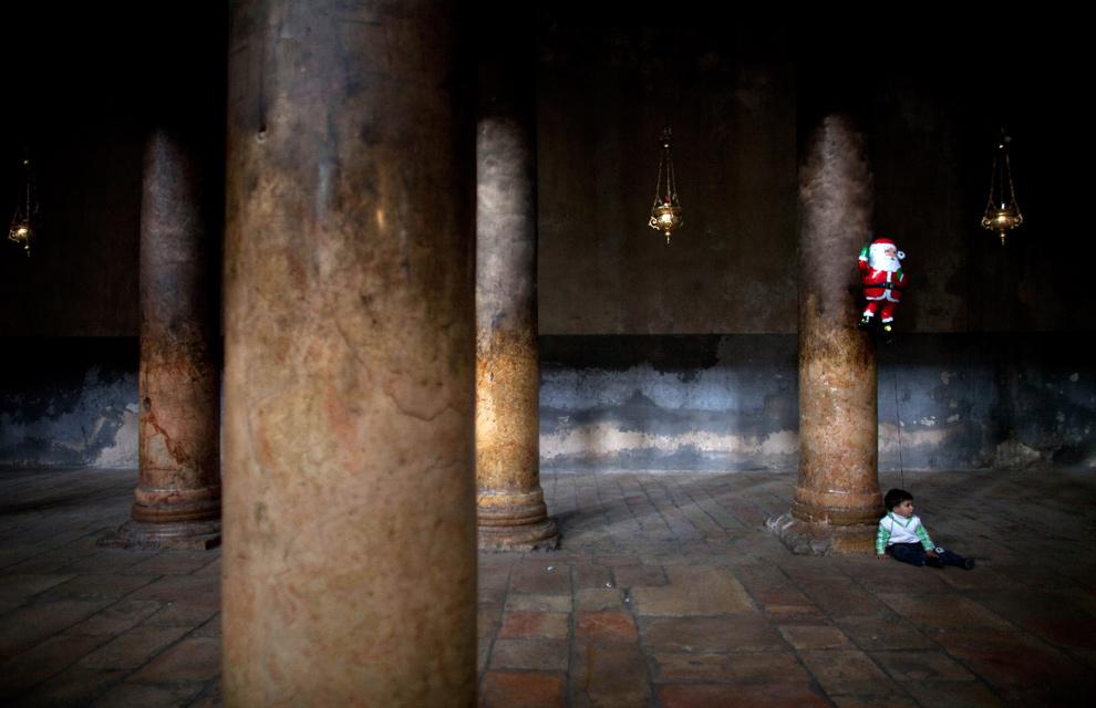 14. Мальчик сидит на земле с шариком в виде Санта Клауса в Рождественском соборе, пока христиане собираются для Рождественских празднеств 24 декабря 2009 года в Вифлееме. (Uriel Sinai/Getty Images)