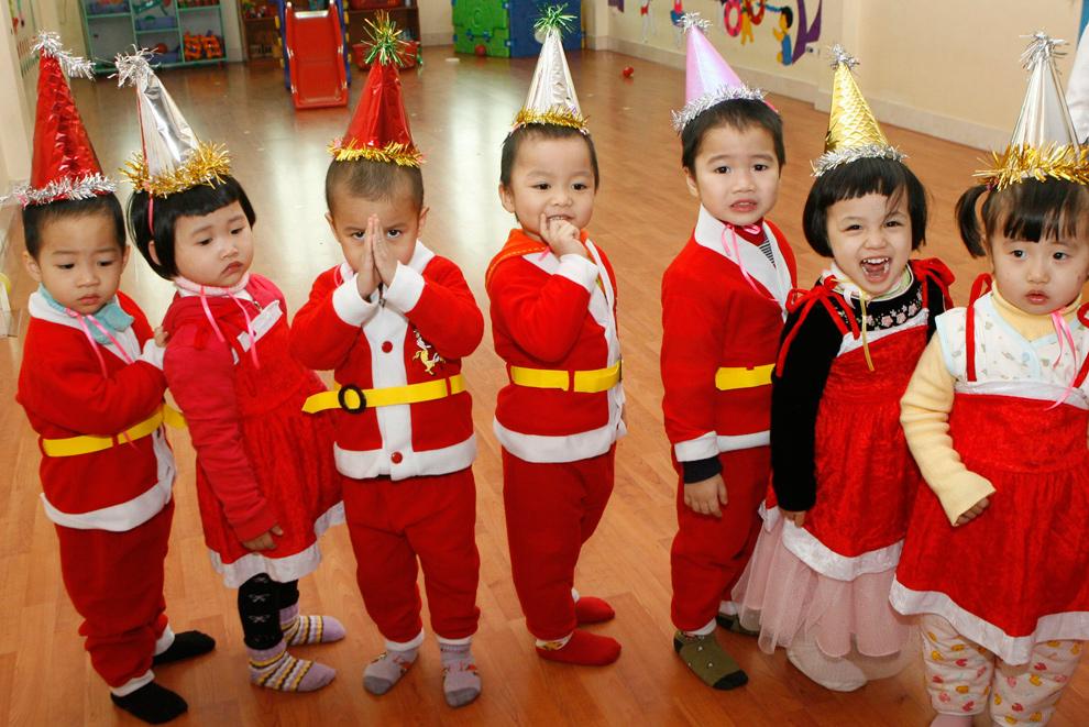15. Дети в костюмах Санта Клауса перед утренником в честь Рождества в детском саду в Ханой, Вьетнам, 24 декабря 2009 года. (REUTERS/Kham)