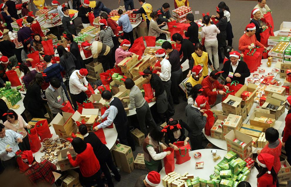 22. Жители Южной Кореи в костюмах Санта Клауса заворачивают рождественские подарки на «Фабрике Санты» 23 декабря 2009 года в Сеуле. «Фаьрика Санты» - это благотворительная организация, которая подготавливает и доставляет подарки бедным людям. (Chung Sung-Jun/Getty Images)