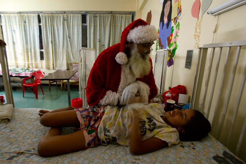 23. 58-летний дантист Франциско Амадор в костюме Санта Клауса навещает больного ребенка в больнице Эскуэла в  Тегусигальпе, Гондурас, 23 декабря 2009 года. (REUTERS/Edgard Garrido)