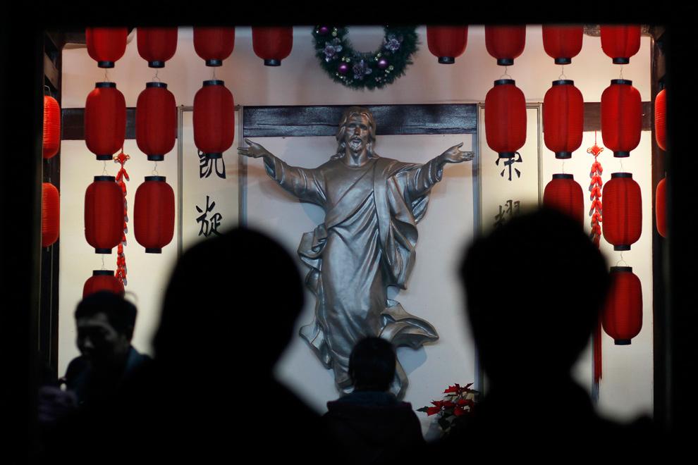 25. Верующие из церкви  Чжуцзяцзяо молятся во время мессы накануне Рождества в Шанхае 24 декабря 2009 года. (REUTERS/Aly Song)