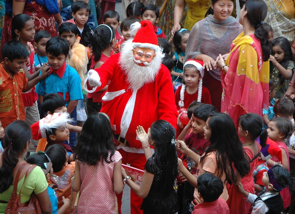 26. Мужчина в костюме Санта Клауса играет со школьниками во время празднования Рождества в Ахмадабаде 23 декабря 2009 года. (AP Photo/Ajit Solanki)
