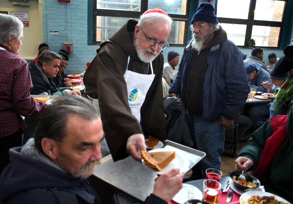 27. Кардинал Шон О'Малли раздает Рождественский ланч бездомным на улице Пайн Стрит в Бостоне. (Boston Globe/John Tlumacki)