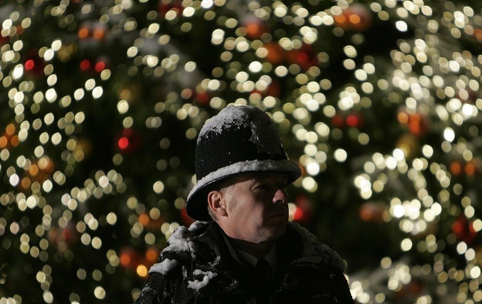 31. Снег падает на офицера британской полиции на фоне елки на улице 10 Downing Street, где живет премьер-министр Великобритании Гордон Браун в Лондоне 21 декабря 2009 года. (AP Photo/Akira Suemori)