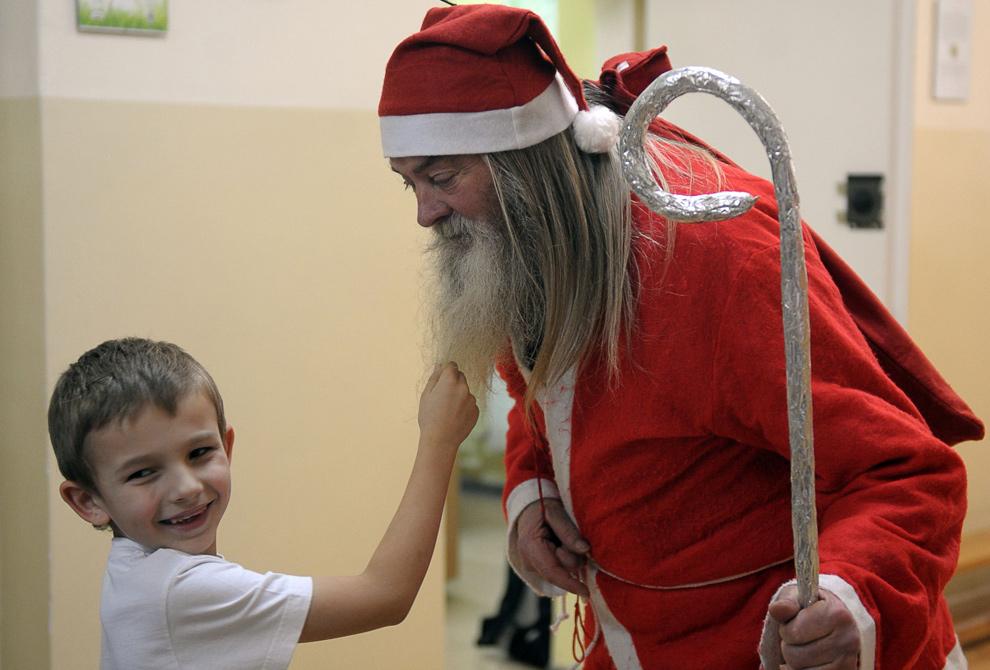 33. 76-летний Ромуалд Мадракивич в костюме Санта Клауса играет с любознательным мальчиком в начальной школе в Костовице, Польша, 15 декабря 2009 года. (JANEK SKARZYNSKI/AFP/Getty Images)