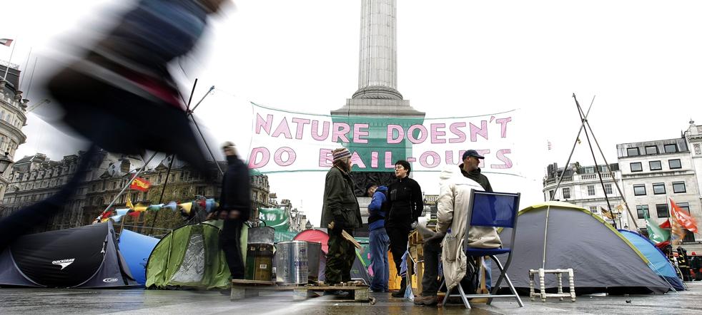 2. Туристы проходят мимо баннера демонстрантов против изменения климата, разбивших лагерь на Трафальгарской площади в Лондоне 7 декабря. Крупнейшая и самая важная конференция по вопросам изменения климата была открыта в Копенгагене. Организаторы предупредили дипломатов от 192 стран, что это может быть последний и самый лучший шанс попытаться защитить мир от последствий изменения климата. (AP/Alastair Grant)