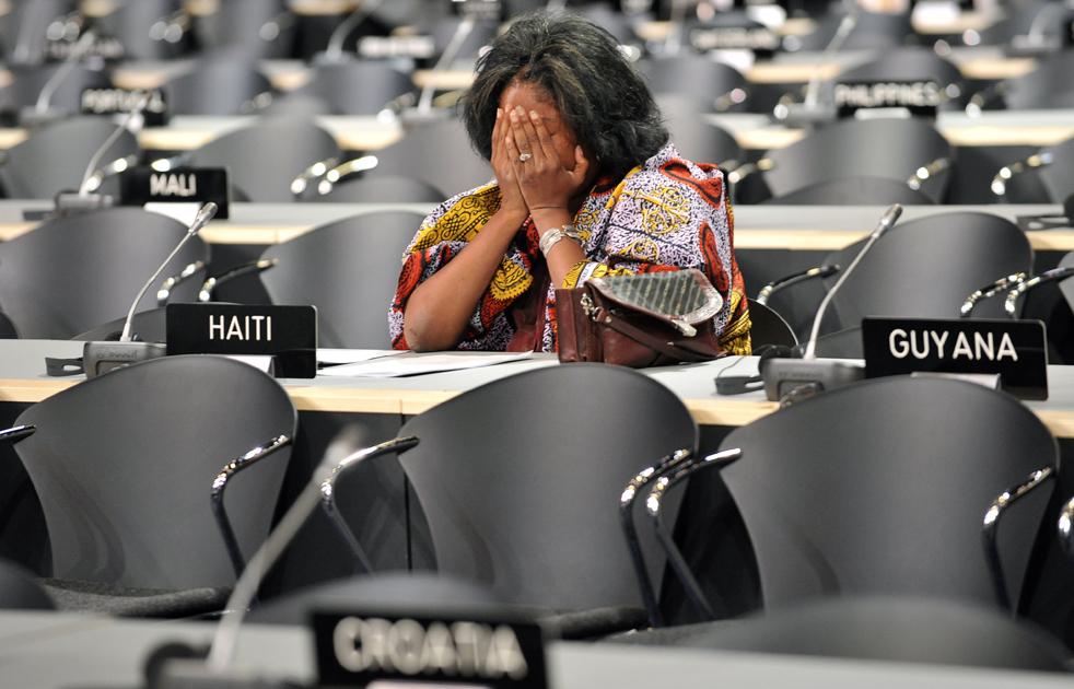 8. Делегат-представитель Гаити отдыхает перед началом заседания на второй день саммита в «Белла-центре» в Копенгагене 8 декабря, когда саммит дошел до главной сути собрания. Делегаты пытались найти компромисс для снижения выброса углерода, а также средства для бедных стран. (AFP/Getty Images/Attila Kisbenedek)