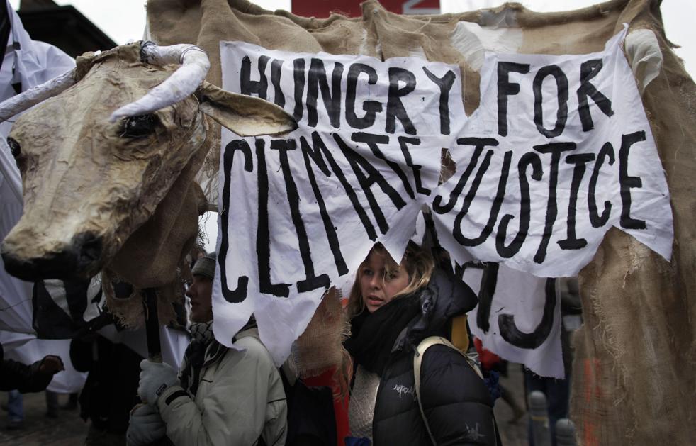 10. Демонстранты идут под плакатом с надписью «Голодные до климатической справедливости» в центре Копенгагена в воскресенье 13 декабря. (AP/Anja Niedringhaus)