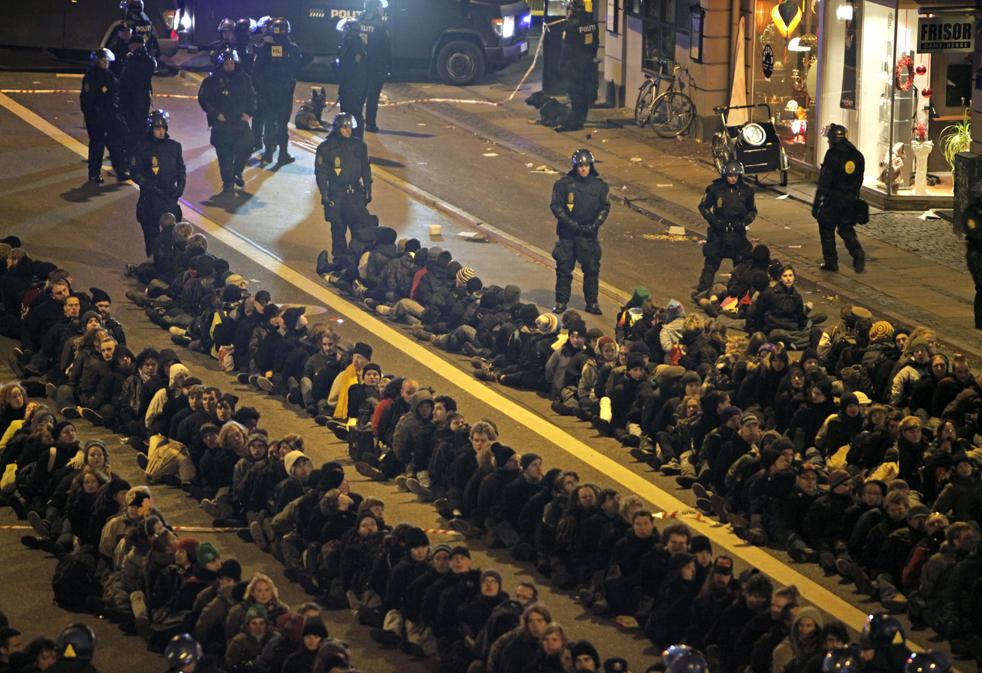 11. Датская полиция пытается разогнать демонстрантов, севших рядами на улице в Копенгагене в субботу 12 декабря. (AP/Thibault Camus)