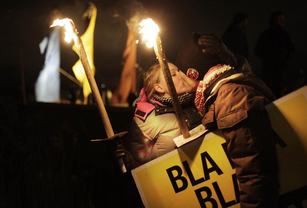 12. Демонстранты целуются во время акции протеста у «Белла-центра» в Копенгагене в субботу 12 декабря. Огромная толпа прошлась с протестами от городского центра до «Белла-центра», где проходила самая крупная и важная конференция, посвященная проблемам изменения климата. (AP/Anja Niedringhaus)