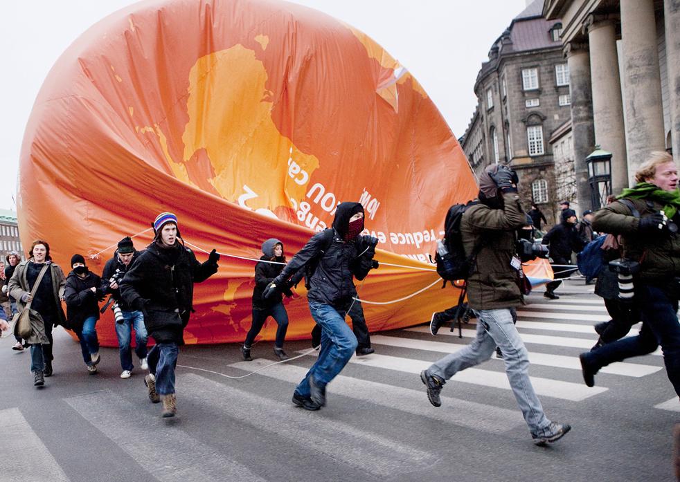 18. Активисты выступающие за защиту окружающей среды из организации «Климат без границ» бегут с украденным воздушным шаром во время демонстрации 14 декабря в Копенгагене на восьмой день климатического саммита ООН. (AFP/Getty Images/Jens Astrup)