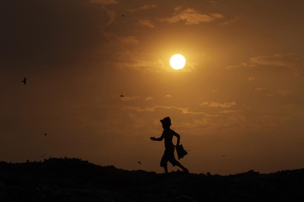 24. Силуэт тряпичника, ищущего вторсырье на свалке на окраине Нью-Дели в воскресенье 13 декабря. (AP/Rajesh Kumar Singh)