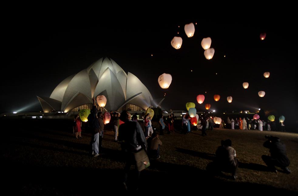 25. Активисты отпускают в небо фонарики, чтобы выразить свои надежды по поводу решений, принятых на климатической конференции в Копенгагене, на фоне храма Лотус в Нью-Дели 10 декабря. (AP/Manish Swarup)