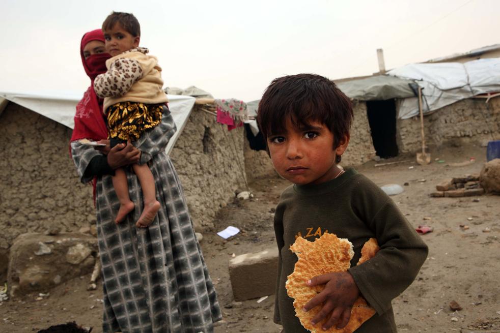 10. Маленький мальчик ждет, пока его родители и другие жители Афганистана получат продовольствие и помощь от ООН 1 декабря в Кабуле. (Getty Images / Majid Saeedi)