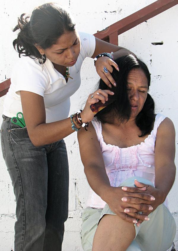 3. Дульче Мария стрижет иммигрантку из Гондураса во время их остановки в Белен Каса дель Мигранте в Салтилло, Мексика, в ноябре 2008 года. (Diana Castillo and Dariela Diaz)