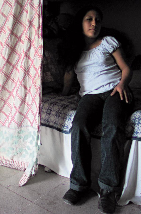 11. Нора из Гондураса сидит на кровати в женском общежитии в пункте для иммигрантов Белен Посада дель Мигранте в декабре 2008 года. (Diana Castillo and Dariela Diaz)