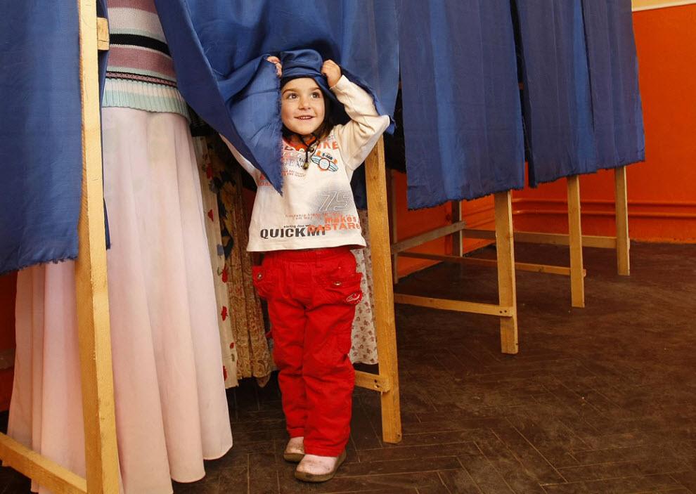 17. Ребенок забавляется с занавеской кабины для голосования, пока члены ее семьи голосуют на президентских выборах в Синсети, Румыния, 22 ноября. (Vadim Ghirda, AP)