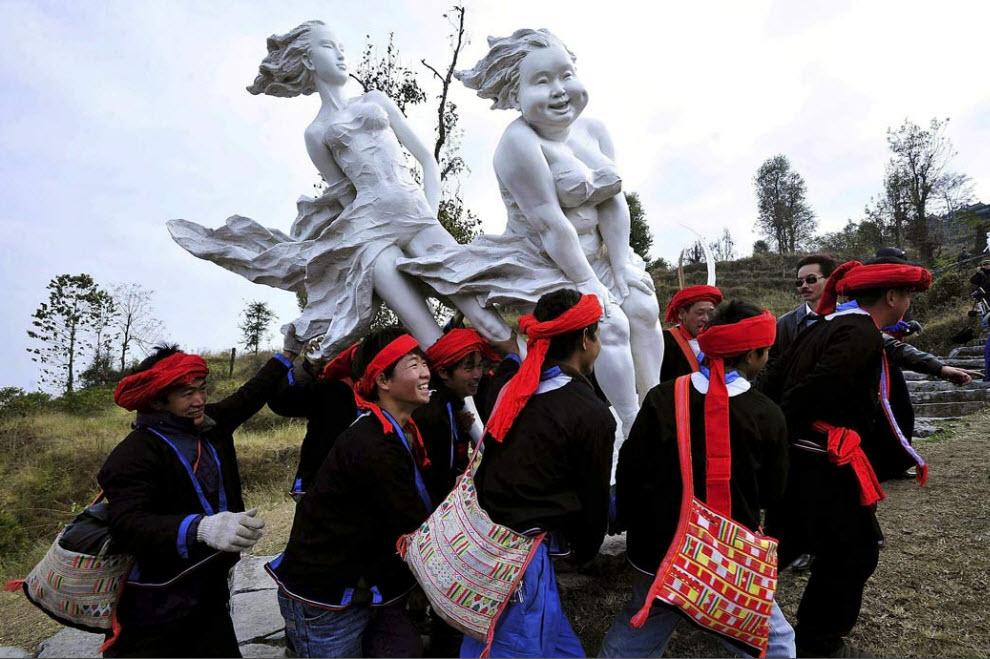 20. Представители этнической группы яо несут произведения искусства китайского скульптора Сюй Хунфэй на передвижной выставке из Гуанчжоу в Ляньнань, Китай, 20 ноября. (AP)