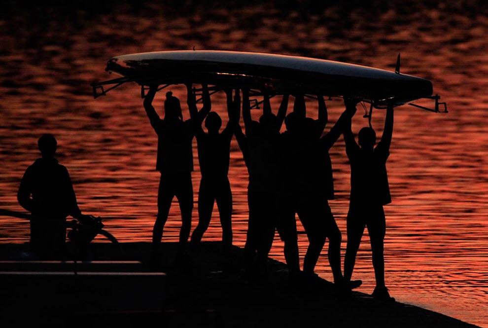 27. Гребцы несут лодку над головами на фоне отражающегося в реке Шуюлкилл солнца в Филадельфии 17 ноября. (Matt Rourke, AP)
