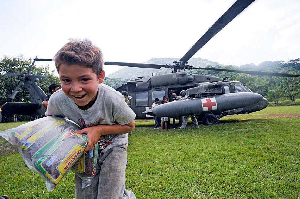 29. Мальчик помогает разгружать продукты с американского военного вертолета в Сан Виченте, Эль Сальвадор, 15 ноября. Эти продукты предназначены для отдаленных деревень в районах, пострадавших от урагана Ида, ставшего причиной гибели 192 человек. (Jose Cabezas, AFP / Getty Images)
