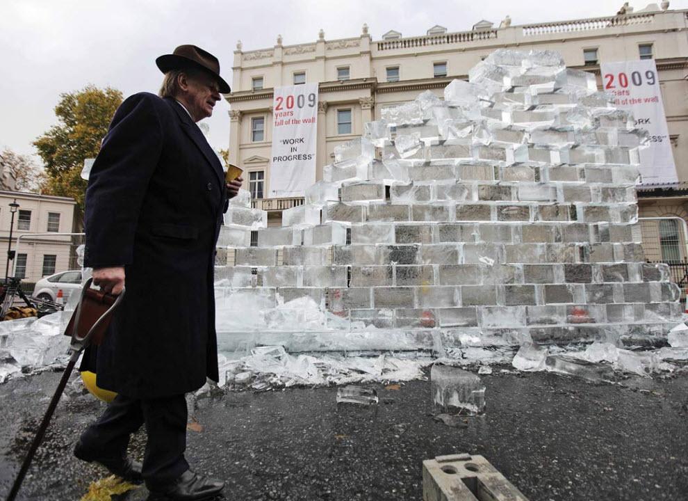 40. Мужчина проходит мимо ледяной стены в 3,5 метра, представляющей Берлинскую стену и являющейся частью инсталляции под названием «Незавершенное произведение» недалеко от Германского посольства в Лондоне 9 ноября. Выставка прошла в честь 20-ой годовщины сноса Берлинской стены в ночь на 9 ноября 1989 года после 28 лет разделения территории Германии. (Lefteris Pitarakis, AP)