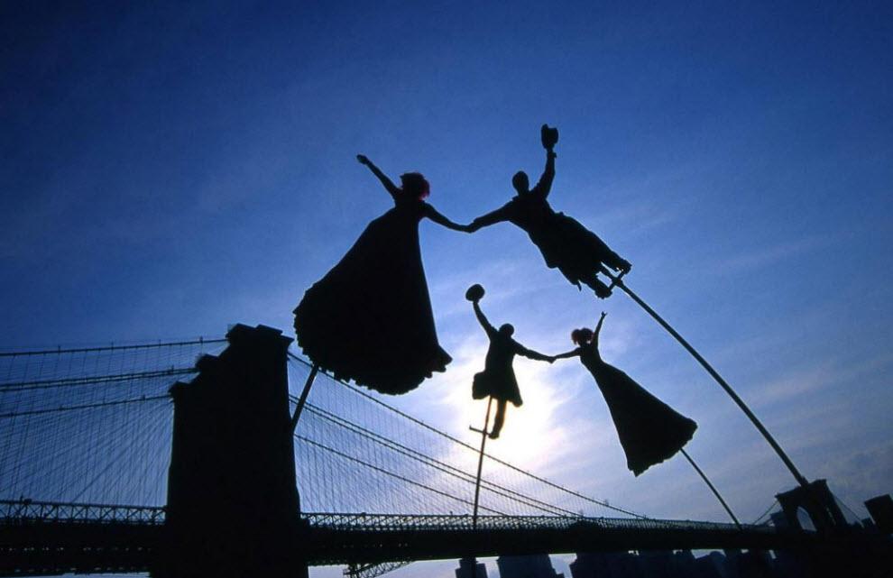 18. Лирические силуэты ходулеходцев, закружившихся в сюрреалистическом танце, на фоне заката над Гудзоном. Воздушный балет проходил под Бруклинским мостом, но достаточно высоко, чтобы зачарованным зрителям пришлось задирать головы. (Peter Guttman)