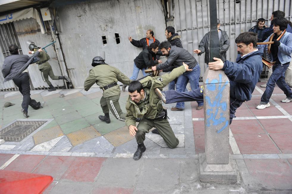 1. Иранские демонстранты бьют офицеров полиции во время антиправительственных протестов в Тегеране 27 декабря. (AP)