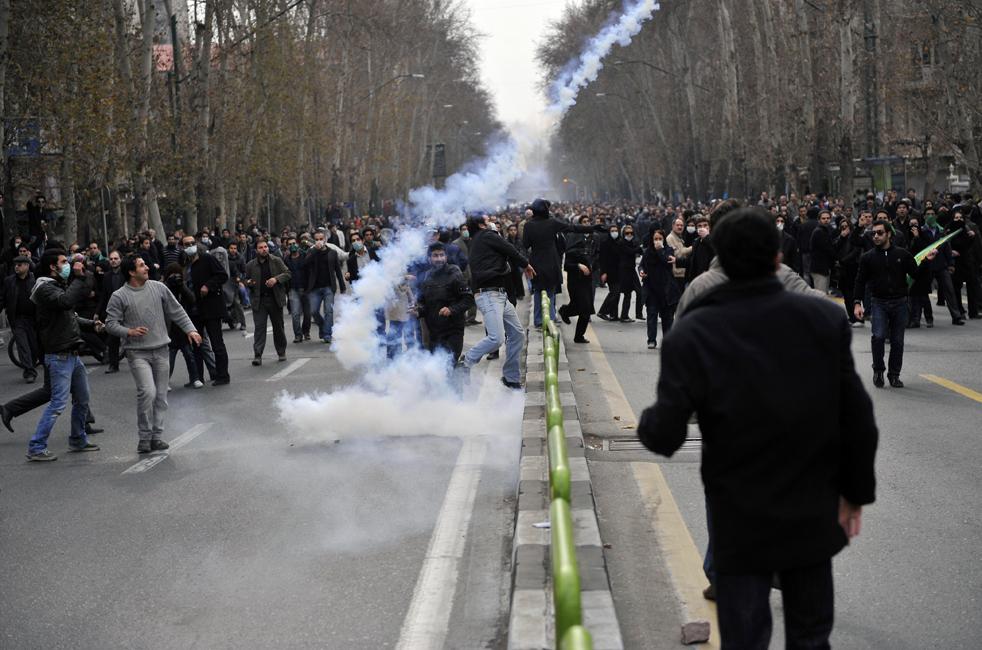 3. Службы безопасности бросают слезоточивый газ в иранских оппозиционеров в Тегеране 27 декабря. (AFP / Getty Images)