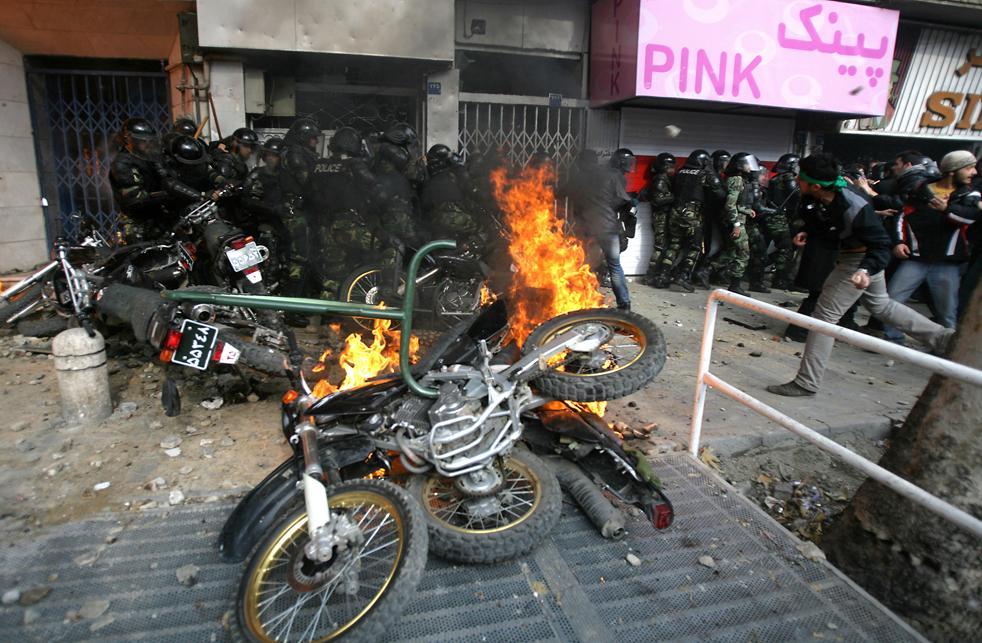 8. Полицейские мотоциклы горят рядом с демонстрантами, бросающими камнями в полицейских в Тегеране 27 декабря. (AFP / Getty Images)