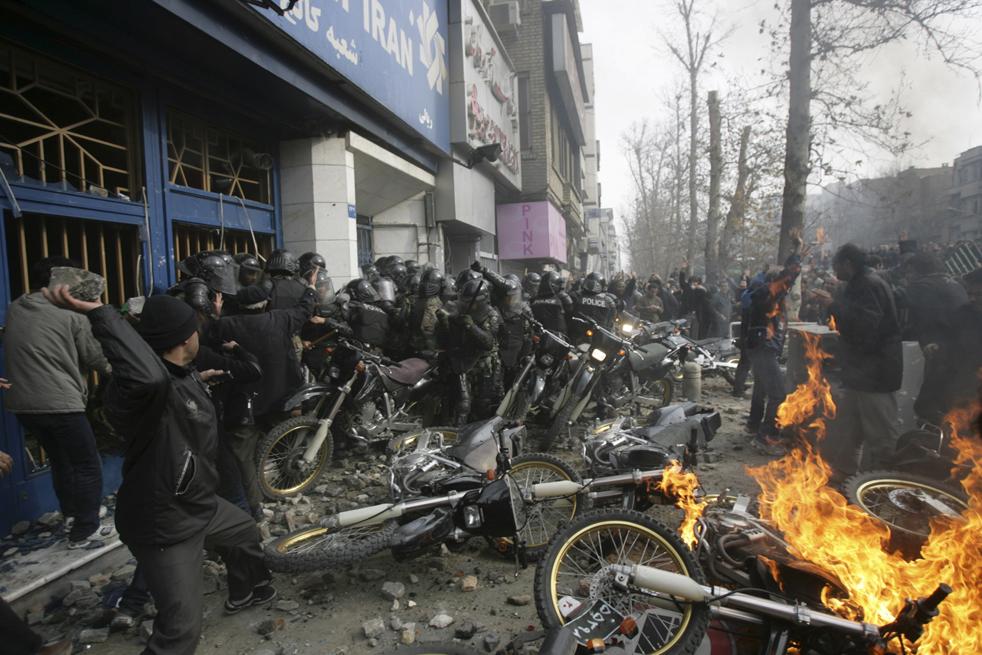 9. Иранский демонстрант (слева) бросает камень в полицейских рядом с горящими мотоциклами во время антиправительственных протестов на улицах Тегерана 27 декабря. (AP)