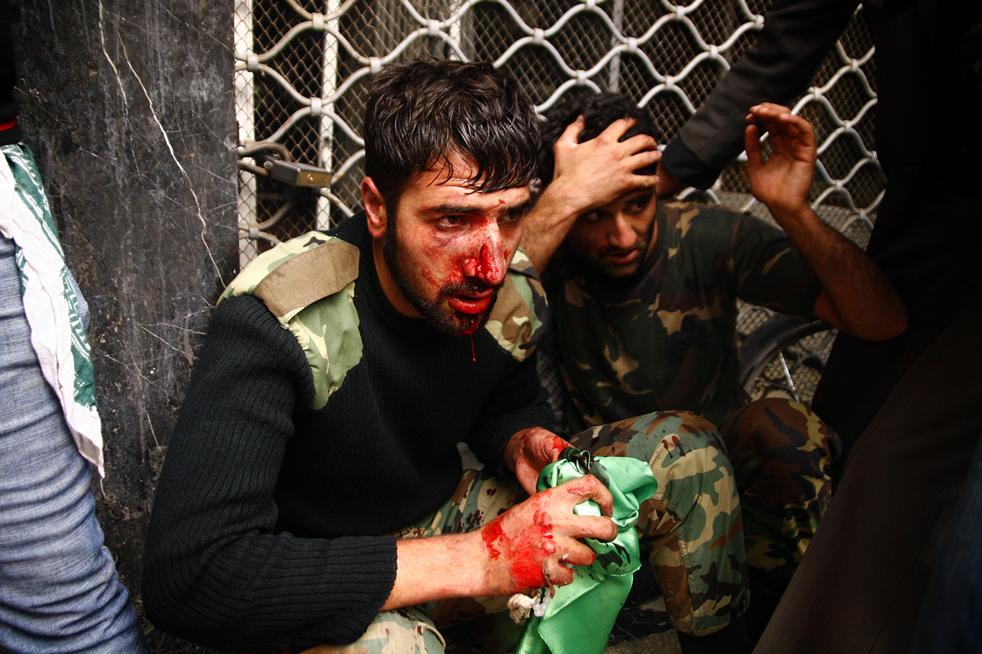 11. Раненые офицеры иранской полиции сидят под защитой сторонников иранской оппозиции во время конфликта на улицах Тегерана 27 декабря. (AFP / Getty Images)