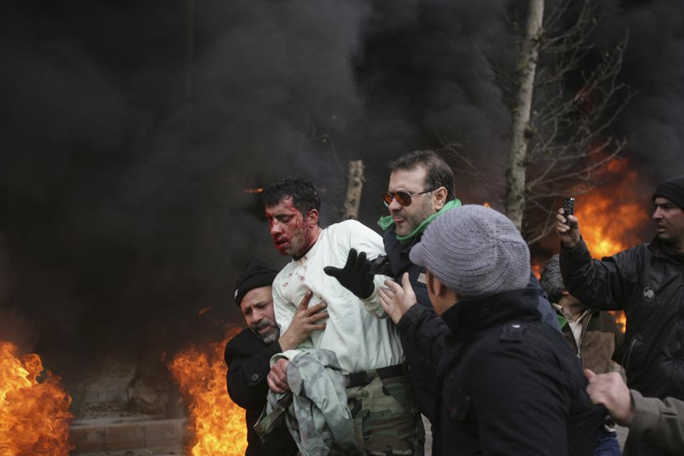 13. Люди помогают офицеру иранской полиции, избитому демонстрантами, уйти в безопасное место во время антиправительственных протестов на улице Революции в Тегеране 27 декабря. (AP)