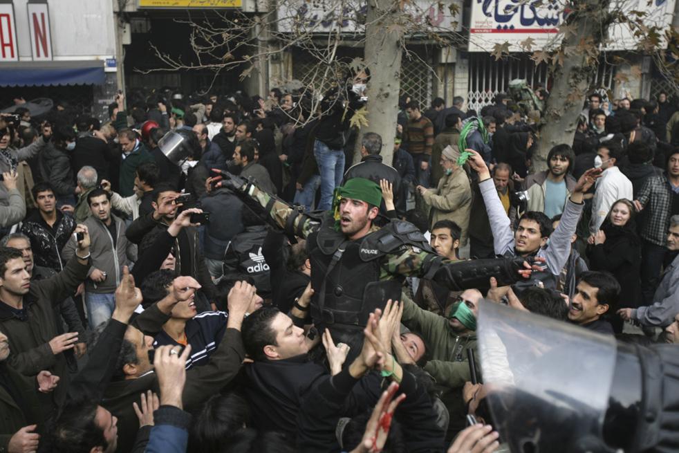 14. Демонстранты держат иранского полицейского, которому на голову повязали зеленый шарф – символ оппозиции – после столкновений на улице Революции в Тегеране 27 декабря. (AP)
