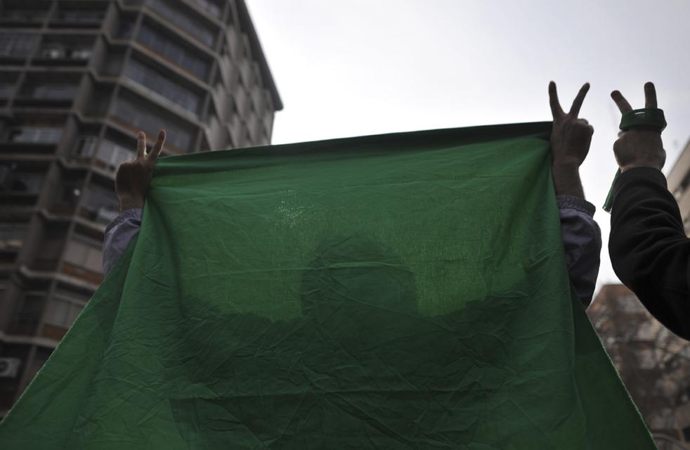 16. Иранские демонстранты держат зеленую ткань – цвет иранской оппозиции – и показывают знаки победы во время антиправительственного протеста в Тегеране 27 декабря. (AP)