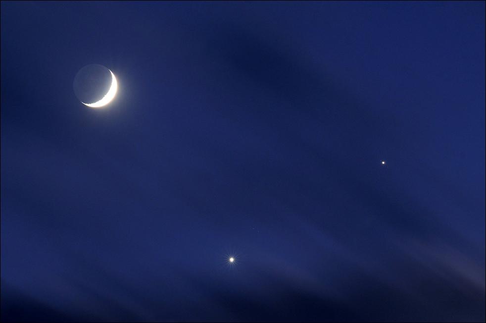 2. На этом снимке с 15-секундной выдержкой, сделанном в Стедмане, Северная Каролина, ночью 1 декабря с помощью телеобъектива, к полумесяцу присоединилась Венера (внизу) и Юпитер (справа). За этой «группировкой» можно было наблюдать с востока США. Ранее в тот же день исследователи в Англии видели, как Луна полностью закрыла Венеру. (AP / The Fayetteville Observer / Johnny Horne)