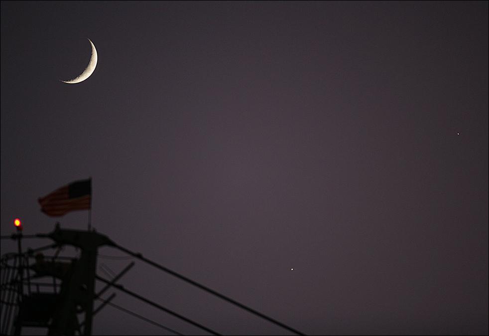 4. Планетарный союз полумесяца, Венеры (в центре внизу) и Юпитера (справа) над американским флагом на строительной вышке медицинского центра в Тайлере, штат Техас, в понедельник 1 декабря. (AP / Dr. Scott M. Lieberman)